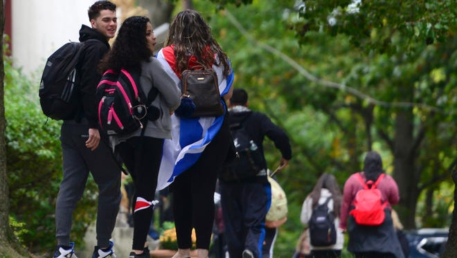A Cliffside Park High School student has a Puerto Rican flag draped over her shoulders as she arrives Oct. 16.