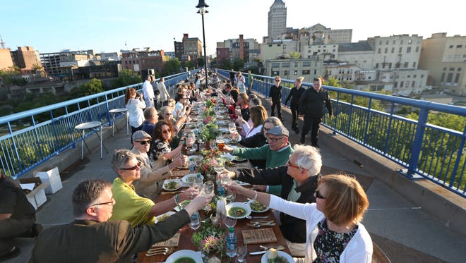 Clockwise from bottom left, Chris DiFrancesco and Kay Aurand of Rochester and Steve and Robin Rauh of Webster are among 200 people toasting at Greentopia's Dinner on the Bridge in 2015.