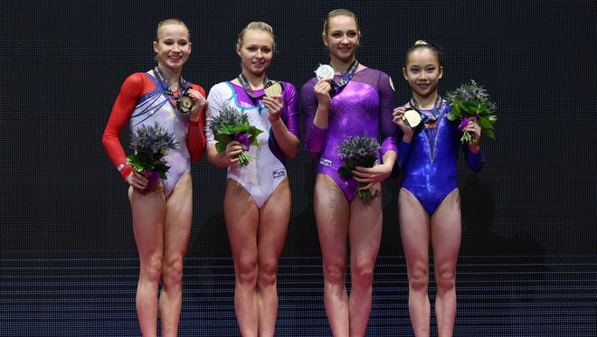 Madison Kocian of United States, Daria Spiridonova of Russia, Viktoriia Komova of Russia and Fan Yilin of China all stand on the podium with their gold medals from the uneven bars final.