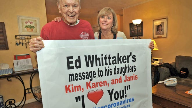 Ed Whittaker, 99, of Weymouth recovered from COVID-19, a stroke and pneumonia to return to his apartment at Gaslight Village. His daughter, Kim Whittaker, of Winchester helped guide his care. They hold a poster Weymouth Elder Services made for him and his three daughters after he came home.  Saturday, June 6, 2020. Tom Gorman/For The Patriot Ledger