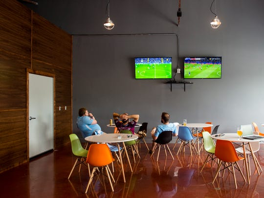 Customers watch a soccer match inside the newly expanded tap room area at Alliance Brewing on Sevier Ave. in Knoxville on Wednesday, May 9, 2018.