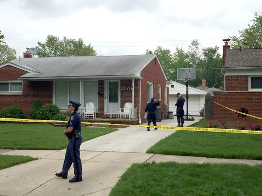 Police officers stand Friday outside of a home on Lochdale in Dearborn Heights, where a Dearborn Heights police officer and another man were found dead, according to police.