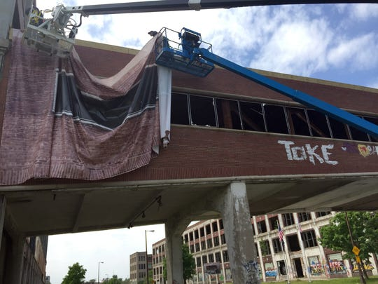 Workmen draped a graphic covering over the iconic brick pedestrian bridge at the Packard Plant. Photo taken May 21, 2015