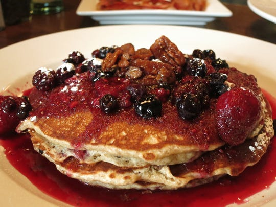 Wheat pancakes topped with warm three-berry sauce,