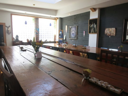 A rustic handmade table, foreground, and a polished conference table, beyond, offer communal seating at Yemans Street restaurant.