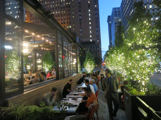 An inviting patio bordered with lighted trees surrounds the glass-walled dining room of the new Townhouse Detroit  downtown.