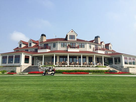 A golf cart passes the clubhouse and hotel at Arcadia