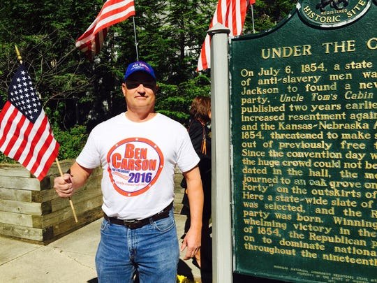 Bob Guyski, a Sharon Township resident and a Dr. Ben Carson supporter, is photographed with the historical marker, Under the Oaks, the birthplace of the Republican party in Jackson on Sept. 23, 2015.