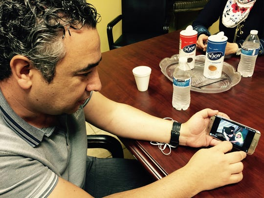 Shadi Martini, of Farmington Hills, senior Syria advistor for Multifaith Alliance for Syrian Refugees, looks at a photo of Syrian refugees in Europe that his group is trying to help with medical clinics in Royal Oak in September 2015.