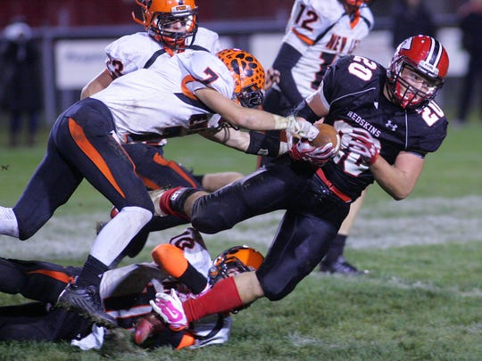 Coshocton junior Jake Fortney carries the ball Friday night as New Lexington senior Mitch Wycinski and sophomore Tanner Wollenberg move in for the tackle. Coshocton won 14-7.