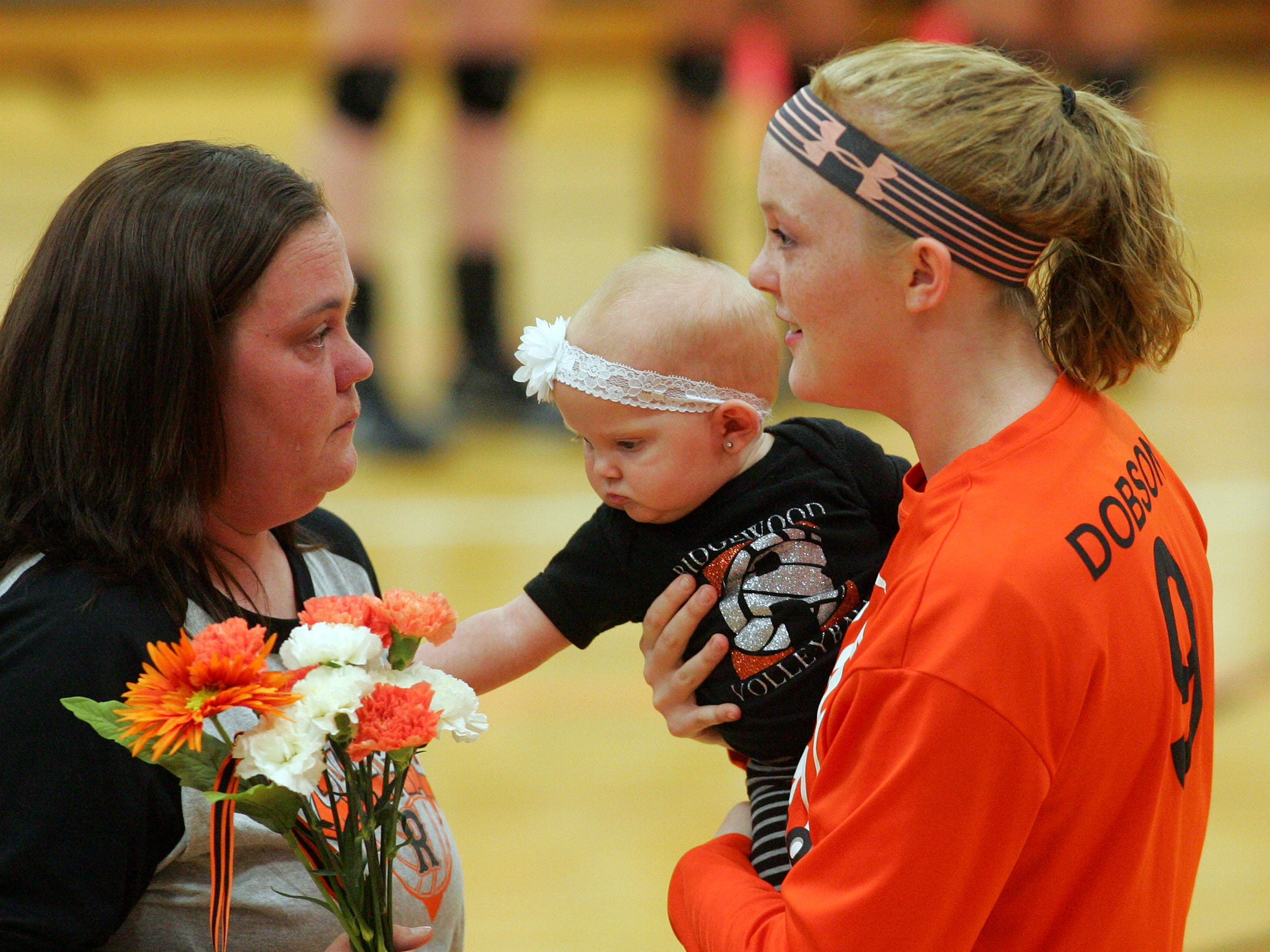 Ridgewood senior Allie Dobson holds her daughter Lillian during senior night Tuesday while her mother Mandy Hayes sheds a tear.