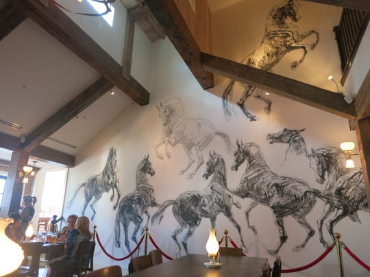 The end wall of the dining room in the Historic White Horse Inn in Metamora features charcoal drawings of horses by a Parisian artist who came to do the work at the request of the inn's owners.