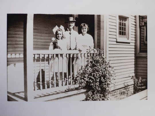 A photograph of a family on the porch of 316 E. Locust