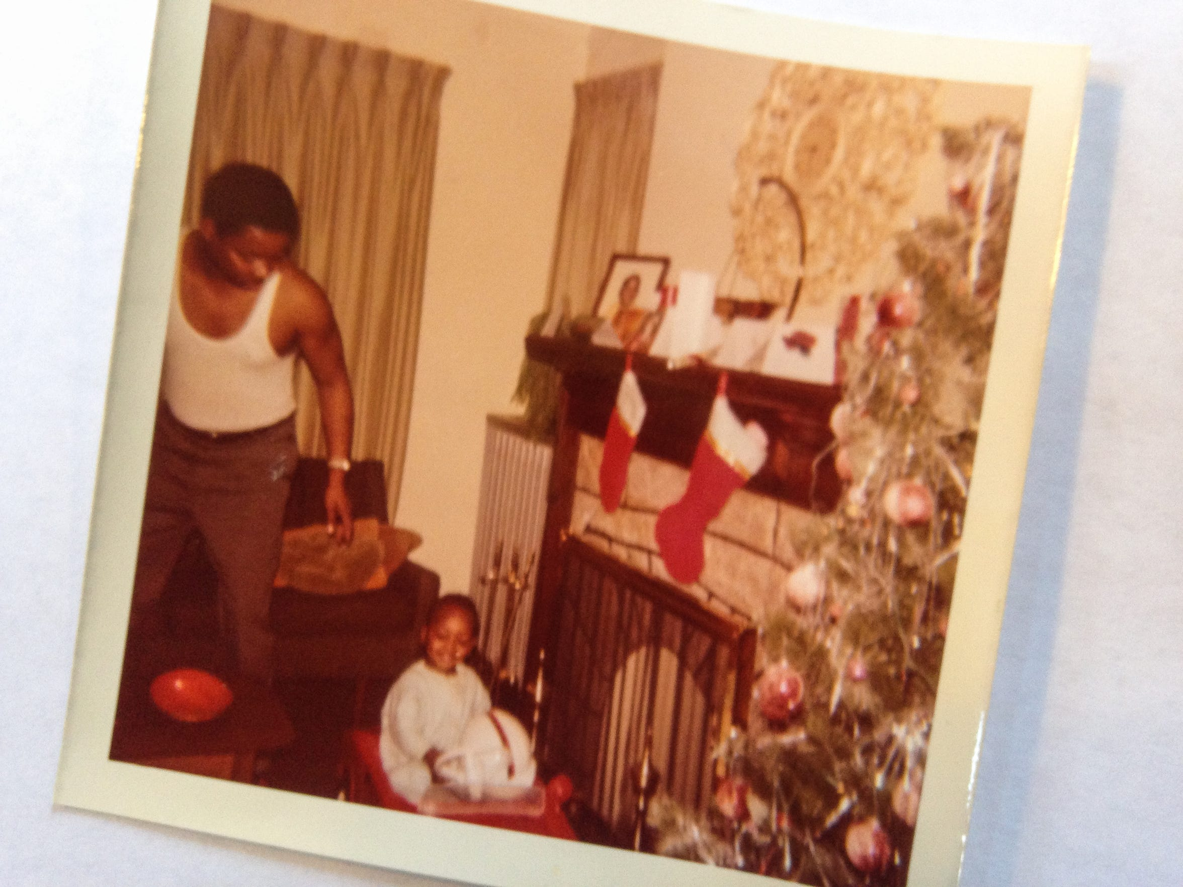 An early 1970s Christmas photo of Free Press Editorial Page Editor Stephen Henderson and his father, Mose Henderson, in the second-floor apartment of 7124 Tuxedo. The house is now abandoned and stripped. Henderson hopes to remake the house as a writers residence and literary center for the neighborhood.
