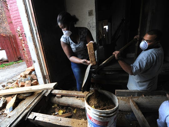 Djuan Freeland, right, the site supervisor for the Youthbuild program at Crispus Attucks, works with student Ashley Demelzile in a rehabilitation of a home along East Maple street on Thursday. Some in the neighborhood have thanked them for their work.