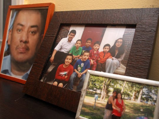 Family photos in the Carrero's Plainfield home include a portrait of Francisco Carrero Servellon, left, Wednesday, December 2, 2015.  Servellon lost his life to cancer in 2013, leaving behind his wife Maria and the couple's eight children.