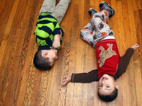Five year old Fernando Carrero plays with his three-year-old brother Rafael, Wednesday, December 2, 2015, on the dining room floor in the family's Plainfield home.