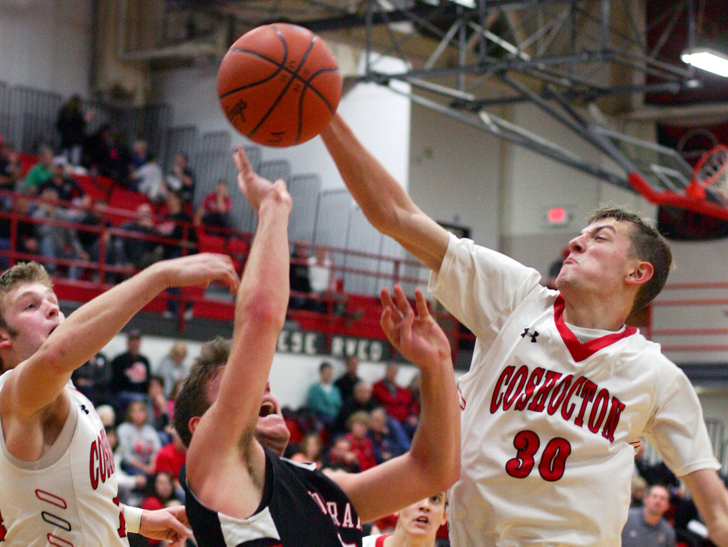 Coshocton senior Conner Roahrig swats the ball from Bishop Rosecrans senior Dominic Mohr Friday during Coshocton's 69-68 loss in overtime.