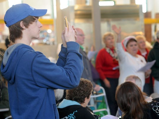 Riley Homsher takes video with his phone of the flash mob, which sang Christmas songs for the visitors at Central Market.