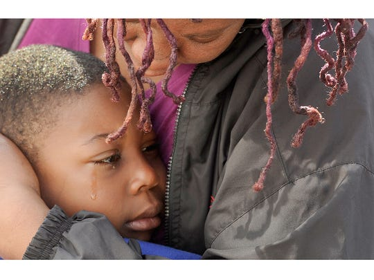 A tearful ZiAire Sweatman-Clark, 7,  is embraced by his family after being returned to his York city home on Saturday, April 18, 2015. ZiAre had been reported missing since Friday and was found safely after spending the night at someone's home without his parent's knowledge.
