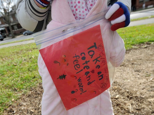 Notes were attatched on coats that were placed throughout Penn Park for people who need them on Saturday morning, Dec. 19, 2015. Tristan Rankin, 7, was inspired to help people who have no coats and collected over 80 coats to spread over three parks in York city with friends and family.