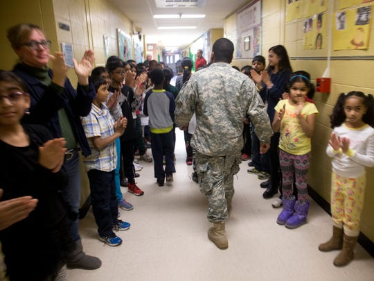 Students line the hallways of James Madison Intermediate School to applaud United States Army private first class Shawn Chavies Jr., Tuesday, December 22, 2015, at James Madison Intermediate School in Edison.
