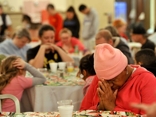 Patricia Ayers of York joins the room in prayer before the buffet is opened Thursday at the A Christmas Smile event at the Elks Club in York..