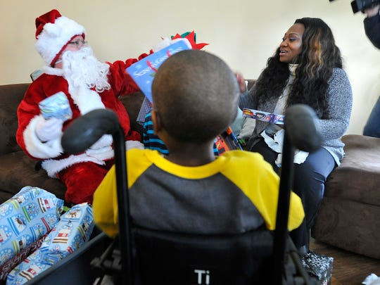 James 'Santa' Heim of Quad Graphics, hands a gift to Sharnette Smith-Kirk in the living room of her Dover Township home. Employees of the company banded together to provide gifts for the children Smith-Kirk rescued from an abusive home.