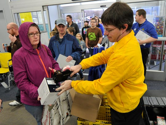 David Rohrman, who works in security at Best Buy in Springettsbury Township, puts tags on items customers returned on the day after Christmas.