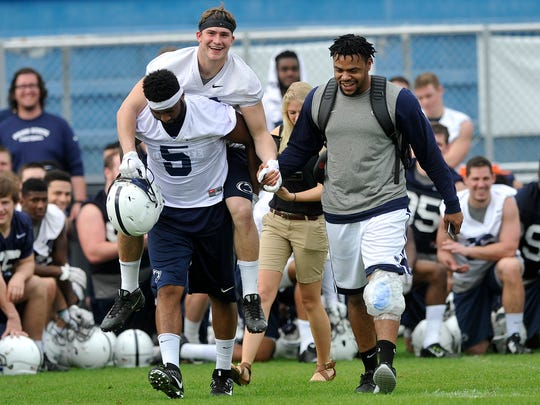 Penn State senior Ben Kline gets carried across the field by teammate Brandon Bell, while Nyeem Wartman-White holds his hand following the Nittany Lions' last practice at Fernandina Beach High School in Fernandina Beach, FL on Thursday, Dec. 31, 2015. The team is preparing to play Georgia in the TaxSlayer Bowl on Saturday, Jan. 2, 2015.