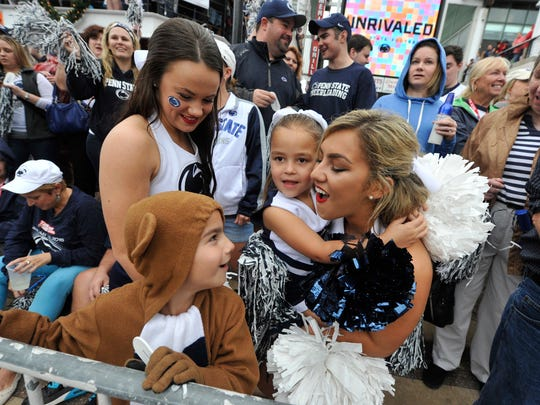 Cheerleaders from Penn State dance and sing with 6-year-old Kara Rhinehart, who is dressed like a cheerleader and her brother Cole, 9, who wearing a Nittany Lion costume. The siblings from Mechanicsburg joined the crowd of Penn State fans on Friday at the Jacksonville Landing for a pep rally to support Penn State ahead of Saturday's TaxSlayer Bowl against Georgia.