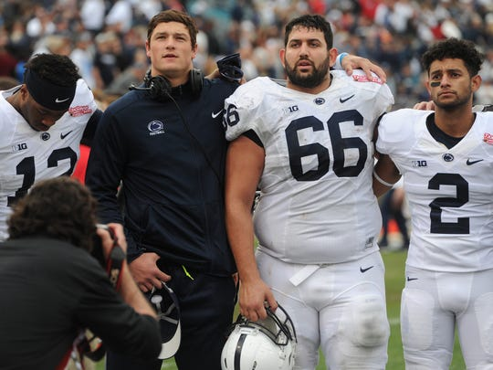 Penn State quarterback Christian Hackenberg puts his arm around senior center Angelo Mangiro while they sing the alma mater after Saturday's loss to Georgia in the TaxSlayer Bowl in Jacksonville, Fla. Hackenberg was knocked out of the game with a shoulder injury, and afterwards he announced he will enter the NFL Draft and skip his senior season.