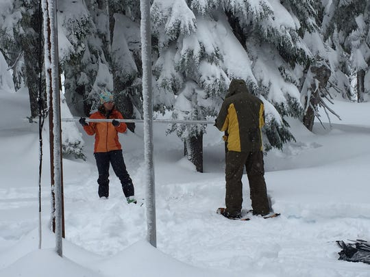 From left, Julie Koeberle, a hydrologist with NRCS, and Dan Fries, a hydrologic technician with NRCS measure snow levels on Mt. Hood, Dec. 29, 2015.