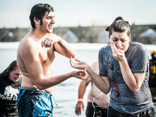 Millersville University student Dylan Huska, left, and girlfriend Alda Janell Dausinger of York College react after walking out of the icy cold Susquehanna River during the Polar Bear Plunge in 2015.