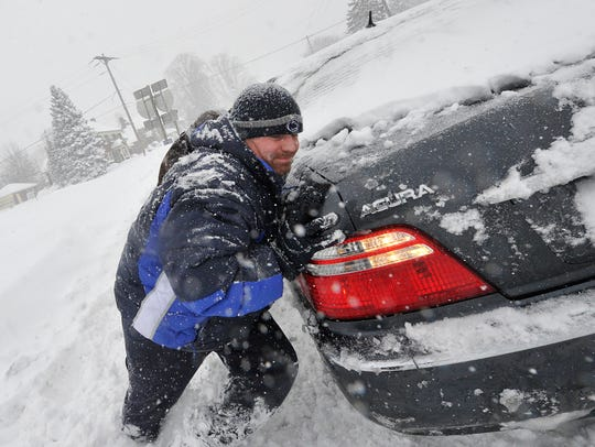 Chad Reams of York helps a stuck driver along East