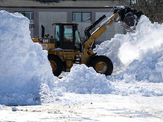A front end loader is used to clear snow from a Route 18 strip mall parking lot, Sunday, January 24, 2016, in East Brunswick.