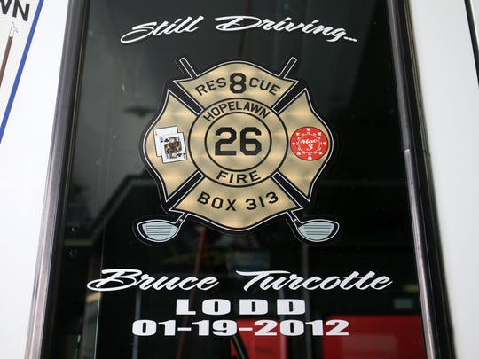 A tribute to Hopelawn volunteer firefighter Bruce Turcotte, who died in the line of duty in 2012, is displayed on a side window of the Hopelawn Engine Company's rescue truck.