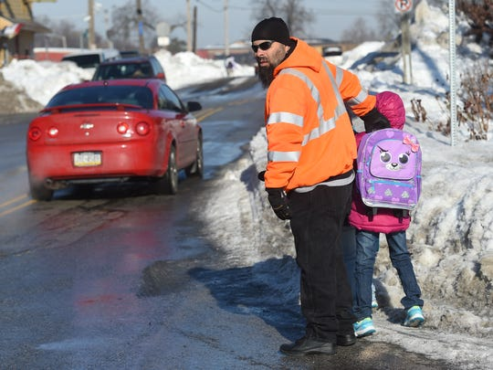 """""""They should have had this cleared,"""" said Antonio Ortiz, who looks out for traffic, after snow-filled sidewalks forced him to walk on North Broad Street, while escorting his daughters, Desiree and Alicia, to Alexander B. Goode K-8 School on Thursday."""