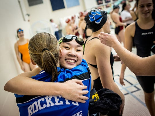 Spring Grove's Abigayle Keating hugs Red Lion's Jessica Sun after Sun placed first in the 100-yard breaststroke during the YAIAA league swimming championship on Friday, Feb. 12, 2016.
