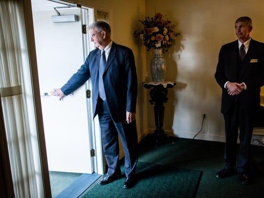 John Keffer, left, opens a door for an attending guest