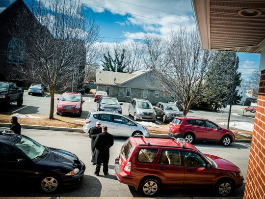 Staff from John W. Keffer Funeral Home wait outside near processional vehicles directing traffic for guests arriving to a service. The family-run business is not uncommon for funeral homes.