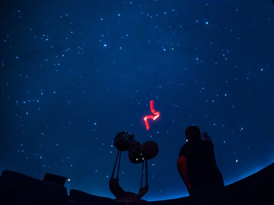Todd Ullery uses a red laser pointer to trace the outline of constellations on the domed ceiling during a stargazing show at the York Learning Center planetarium on March 6.