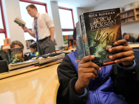 """Tebyus Peyton, a fifth grader at Jackson K-8 school, reads along with his teacher Jonas Lau, rear, as the class works through another chapter of """"Percy Jackson."""" York City School District's revised recovery plan focuses on infrastructure, including rewriting the math and English language arts curriculum."""