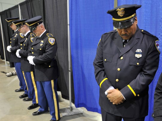 Officers with the York City Police Department bow their heads in prayer for retired York City Police officer and Schaad Detective Agency security officer Ronald Heist during a memorial service at the Utz Arena of the York Expo Center on Saturday.