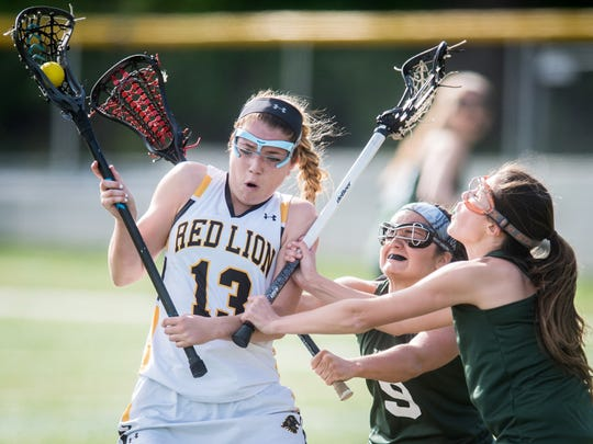 York Catholic's Maura Palandro (9) and Peyton Feder (4) defend against Red Lion's Alyssa Adams (13) in a YAIAA girls' lacrosse game at Horn Field on Tuesday, April 19, 2016. York Catholic won 22-4.