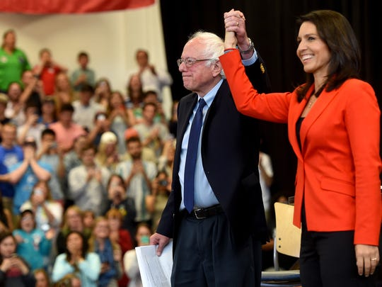 Senator Bernie Sanders raises the hand of Congresswoman Tulsi Gabbard, who introduced the presidential candidate, for his town hall meeting at Gettysburg College on Friday, April 22, 2016.