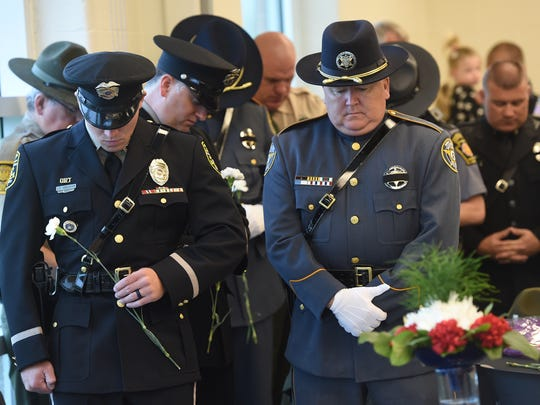 Memorial of various police departments bow their head in prayer during the annual police memorial service.