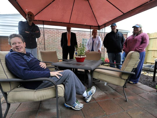 Charlie Holtzinger takes a seat beneath the canopied patio that is part of the back yard renovation his wife, friends and family did to surprise him after recent surgery. Denise Holtzinger said her husband needed a place to read and recuperate.