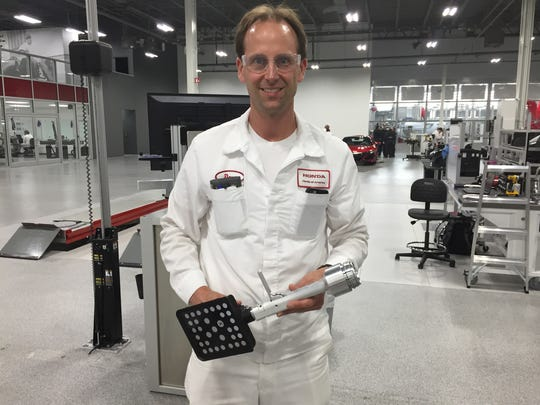 Doug Duff, assistant chief inspecting engineer, holds a tool he created that is used to help align the tires on the 2017 Acura NSX.