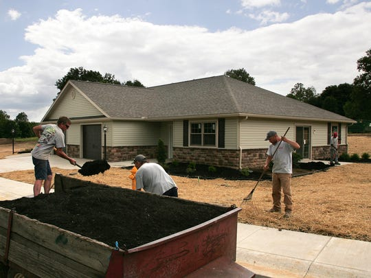 Dane Unger Landscaping employees spread mulch around one of the 12 condominiums at Country Club Condos on Cambridge Road in Coshocton.